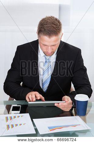 Stylish Hardworking Businessman Using A Tablet Computer
