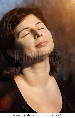 Beautiful Woman Is Relaxing Outdoor With Closed Eyes