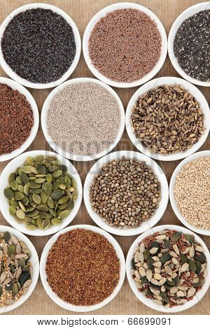 Healthy seed super food selection in white porcelain bowls.