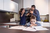stock photo of argument  - Sad child suffering and his parents having hard discussion in a home kitchen by couple difficulties - JPG