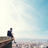 picture of parkour  - Young man sitting on a roof and looking city - JPG