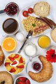 stock photo of bagel  - Breakfast table with a cereals bagels marmalade coffee and orange juice from above - JPG