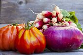 stock photo of boeuf  - Coeur de Boeuf Tomatoes large red Onions and Radishes fresh from the Weekly Market on a old wooden Table - JPG