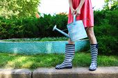 image of woman boots  - Young woman in rubber boots holding watering can - JPG