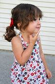 foto of bow-legged  - A little girl with pigtails and red bows looking like she - JPG
