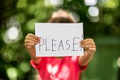 picture of politeness  - Blurred girl holding a piece of paper with the word Please in front of her - JPG