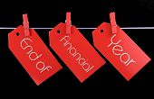 stock photo of peg  - End of Financial Year red ticket sale tags hanging from pegs on a line against a black background - JPG