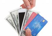 foto of payment methods  - Hand holding banknotes credit cards and a tablet with a second hand selecting the tablet as a method of purchase and payment for merchandise isolated on white - JPG