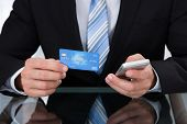 stock photo of card-making  - Businessman doing online banking or making a purchase through an online store using his dank credit card and a mobile phone close up view of his hands - JPG