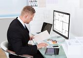 stock photo of collate  - Businessman analyzing a spreadsheet online checking against a document in his hand to collate the information - JPG