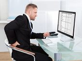 stock photo of stiff  - Businessman rubbing his back as he sits working at his desk in font of his large desktop monitor as he eases the stiffness - JPG