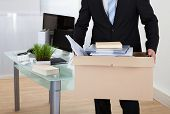 image of packing  - Businessman moving offices packing up all his personal belongings and files into a brown cardboard box - JPG