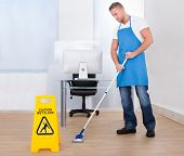 picture of janitor  - Yellow warning notice to caution people to a slippery wet surface as a janitor mops the floor in an office building - JPG