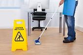 stock photo of cleanliness  - Yellow warning notice to caution people to a slippery wet surface as a janitor mops the floor in an office building - JPG
