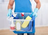 pic of apron  - Janitor or cleaner wearing an apron and gloves carrying a tub of cleaning supplies as he goes about his work at the office - JPG