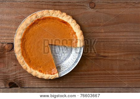 A pumpkin pie with a slice cut out. Horizontal format on a rustic wood table.