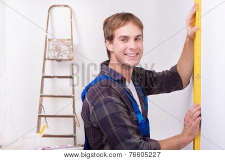 Repairman measuring with builder level