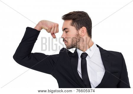 Cheerful businessman tensing arm muscle on white background