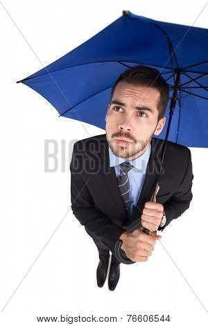Anxious businessman under umbrella looking up on white background