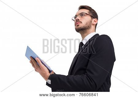 Businessman looking away while using tablet on white background
