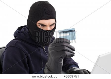 Burglar using credit card and laptop on white background