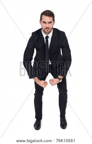 Smiling elegant businessman flexing muscles on white background