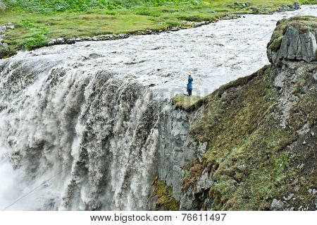 Unrecognizable photographer is taking pictures of Hafragilsfoss, very powerful waterfall. It is located in Jokulsargljufur National Park the northeasten Iceland on the river Jokulsa a Fjollum.
