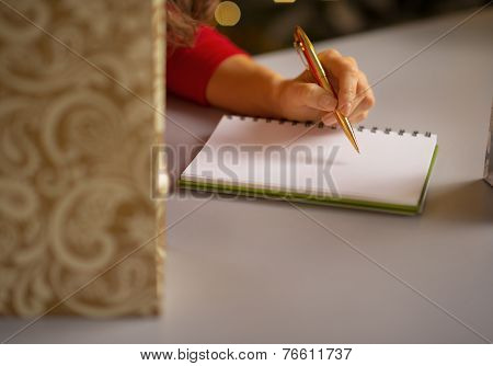 Closeup On Young Woman Writing In Notebook List Of Christmas Pur