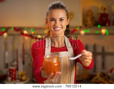 Happy Young Housewife Giving Homemade Orange Jam