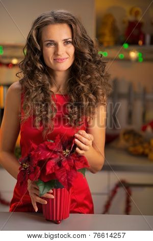 Portrait Of Thoughtful Young Woman With Christmas Rose In Kitche