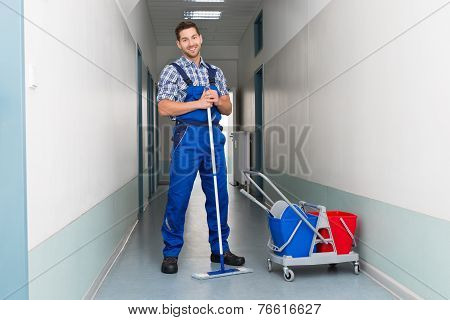 Happy Male Worker With Broom Cleaning Office Corridor