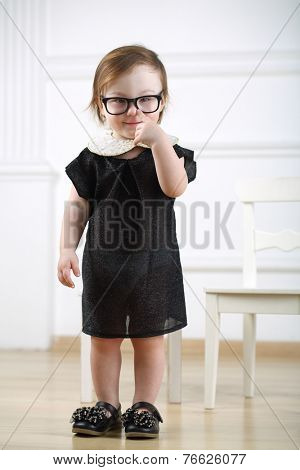 Portrait of little girl in black dress and glasses putting finger to nose