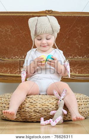 Little girl in knitted hat with hare ears sitting on pouf with Easter eggs and toy bunny