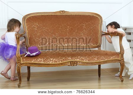 Little boy and girl playing hide and seek around sofa