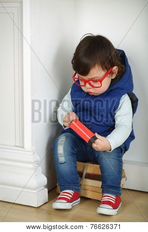 Little boy in red with glasses sitting on a bunch of old books in a corner
