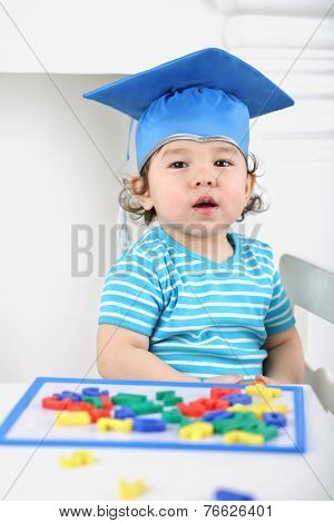 Portrait of small boy in blue graduation hat sitting at table with children magnetic board with colored letters
