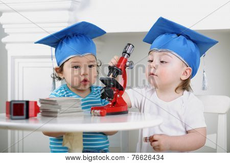 Small children in blue graduation hat adjust microscope on table
