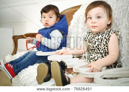 Beautiful little girl sitting on couch next to boy and holding white wooden sign family on her lap