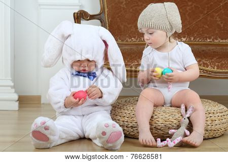 Little boy and girl in costumes bunny sitting on floor with Easter eggs