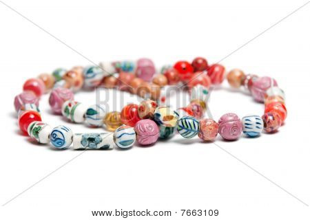 A Necklace With Beads In Various Colors And Patterns