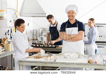 Portrait of happy male chef standing arms crossed while colleagues preparing pasta in commercial kitchen