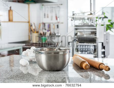 Mixing bowl with eggs and rolling pin on countertop in commercial kitchen