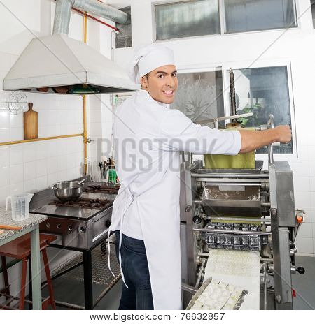 Portrait of smiling male chef processing pasta sheet in machinery at commercial kitchen
