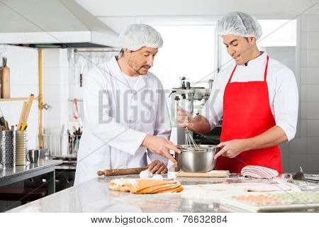 Male chefs discussing while preparing ravioli pasta at commercial kitchen counter