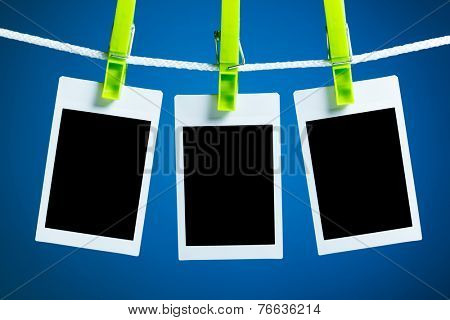 blank photos hanging on rope, blue background