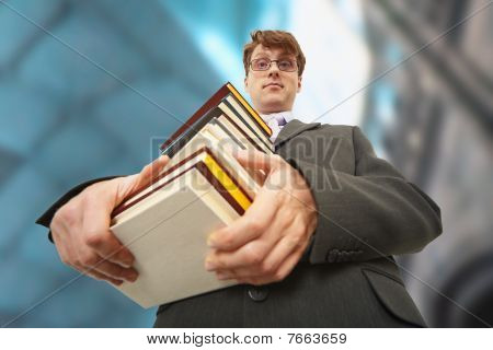 Librarian Holding Pile Of Books