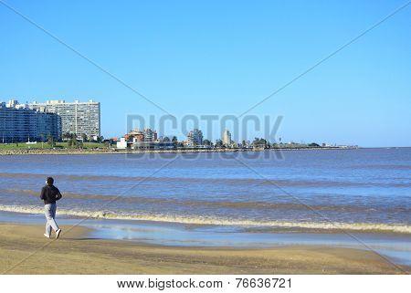 alone man run along seaside in Montevideo