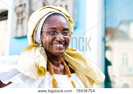 BAHIA, BRAZIL - CIRCA NOV 2014: A Brazilian woman of African descent, smiling, wearing traditional clothes from the state of Bahia in the old colonial district of Salvador (Pelourinho).