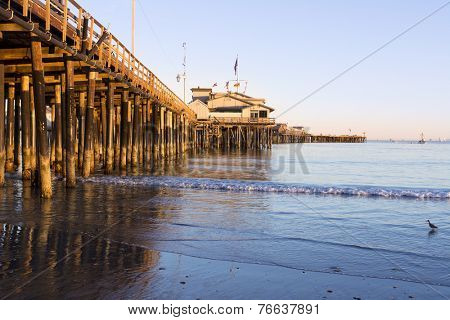 A low, setting sun casts a deep orange light on the pilings of the Santa Barbara pier, also know as Stearns Wharf.