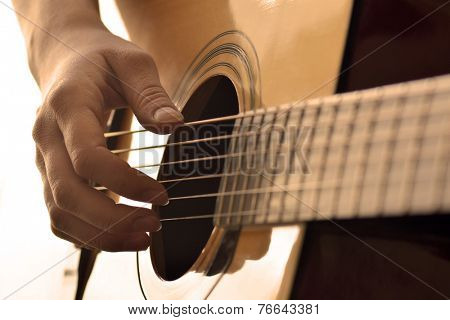 Playing guitar strings and frets for making music